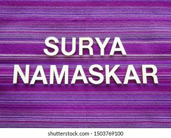 "Wooden text letters with the Sanskrit words""SURYA NAMASKAR"" for a sign, banner, placard or wallpaper on a vibrant purple woven texture background"