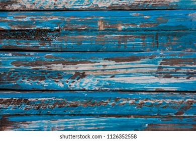 Wooden texture with weathered, chipped blue paint