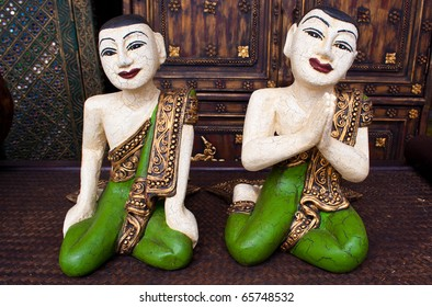 """Wooden Thai statues with hands in """"sawasdee"""" greeting pose"""