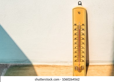 Wooden thermometer leaning against a white wall with floorboards