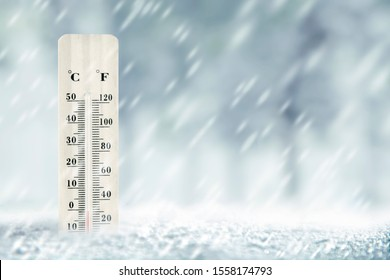 Wooden thermometer with the low temperature at winter with snowfall background