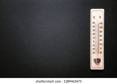 Wooden thermometer on black background.