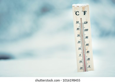 Wooden thermometer in the snow. Four degrees Celsius on the plus after snowfall.