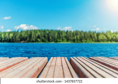 Wooden timber of a rural mooring on a lake in the middle of the forest. A peaceful river dock in the woods.Sunny footbridge. Minimal background with blue sky,clean lake and mooring in the country side - Shutterstock ID 1437837722
