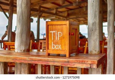 Wooden tip box on table counter. Bar Restaurant Cafe blurred background. Tips and donation concept, money savings. Gratification for good quality of customer service.