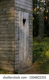 Wooden toilet at the edge of the forest on a sunny summer morning
