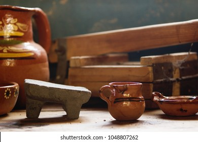 Wooden tortilla making machine and clay dishes, mexican kitchen, metlapil, metate