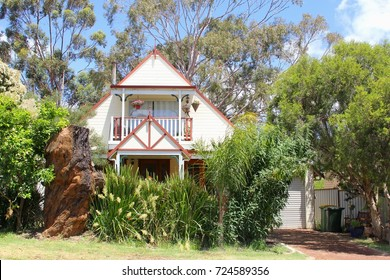 Wooden townhouse with balcony, garage, forest trees and green plants in front yard garden, Western Australia