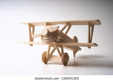 Wooden toy airplane on old white background