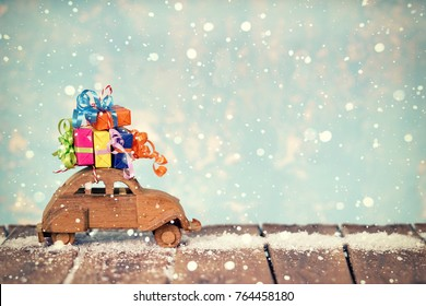 wooden toy car with christmas gifts on rustic wooden table