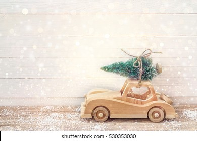 Wooden Toy Car with Christmas tree on the roof on a wooden table. Christmas background. Holidays card. Copy space.