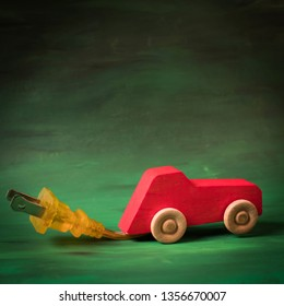 Wooden toy car with an electric plug for charging. Electric auto concept. Green, sustainable transportation technology. Save money and resources with environmentally friendly car. The future is green.