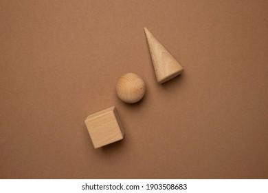 Kindersorter aus Holz mit kleinen Holzdetails in Form von geometrischen Formen, Rechteck, Dreieck auf braunem Hintergrund, Draufsicht auf dem Figurenkonzept