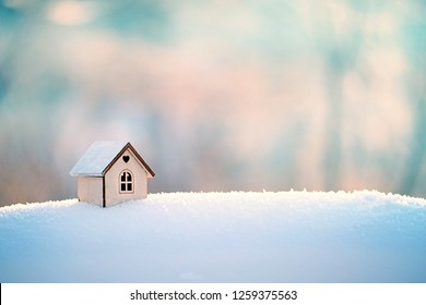 Wooden toy house standing in winter snow background. Concept of winter, Christmas and new year, cozy, loving, protecting. house in winter nature. House concept construction, sales, rental