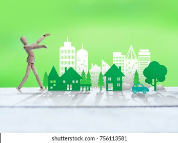 Wooden toy man and green environment city, ecology concept
