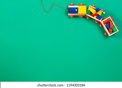 Wooden toy train with colorful blocks on green background