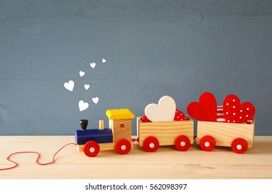 Wooden toy train with hearts on the table.
