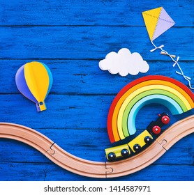 Wooden toy train, railway for preschool child, wood rainbow, paper crafts on blue table. Waldorf or montessori school background. Kids dream, travel concept. Educational toys for kindergarten children