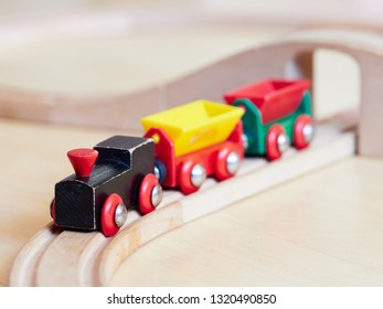 Wooden toy train running on miniature tracks. The black engine pulling colorful cars on the floor. Educational toys for children in preschool and kindergarten.