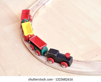 Wooden toy train running on miniature railroad. The black engine pulling colorful cars on the floor. Educational toys for children in preschool and kindergarten.