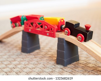 Wooden toy train running on miniature railroad bridge. The black engine pulling colorful cars on the floor. Educational toys for children in preschool and kindergarten.