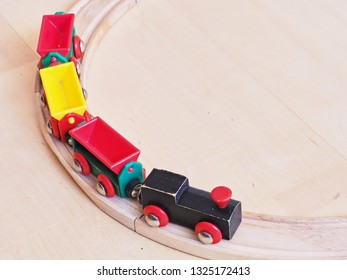 Wooden toy train running on miniature railroad tracks. The black engine pulling colorful cars on the floor. Educational toys for children in preschool and kindergarten.