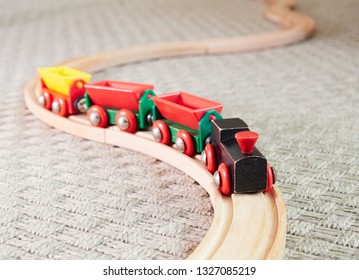 Wooden toy train running on miniature tracks. The black engine pulling colorful cars on the carpet. Educational toys for children in preschool and kindergarten.