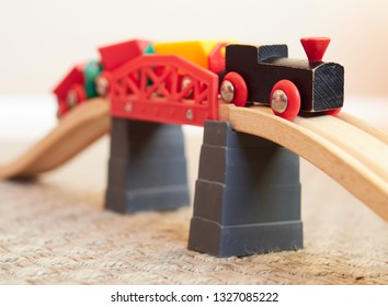 Wooden toy train running on miniature bridge. The black engine pulling colorful cars on the floor. Educational toys for children in preschool and kindergarten.