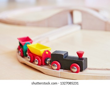 Wooden toy train running on miniature railway tracks. The black engine pulling colorful cars on the floor. Educational toys for children in preschool and kindergarten.