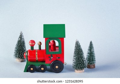 Wooden toy train surrounded by christmas trees
