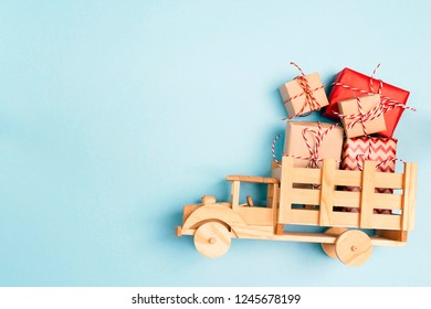 Wooden toy truck  with Christmas gift boxes on blue background and copy space. Top view.