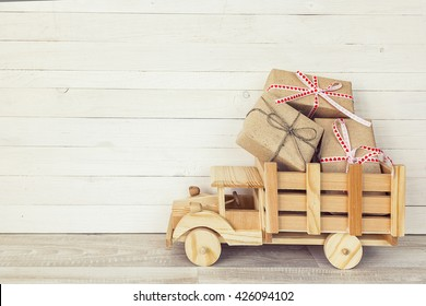 Wooden toy truck with gift boxes in the back on a white wooden background. Place for text.