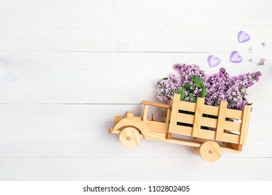 Wooden toy truck with lilac flowers in the back on white wooden background. Space for text. Festive greeting concept.