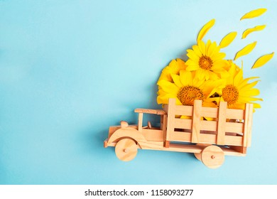 Wooden toy truck with yellow sunflowers in the back on blue background. Space for text. Festive greeting concept.