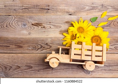 Wooden toy truck with yellow sunflowers in the back on rustic background. Space for text. Festive greeting concept.