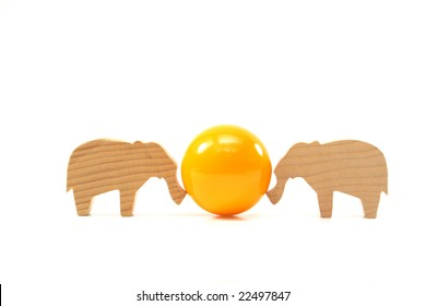 Wooden toys elephants push the ball on white