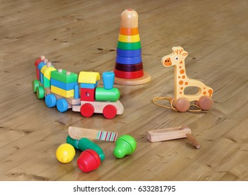 wooden toys on wooden floor. Colorful toys made from wood. Train from blocks in different shapes. Giraffe with wheels and twine for pulling. Color tower, geometric shapes. Fruits to slicing. Rattle