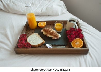 Wooden tray with breakfast in bed and red roses petals