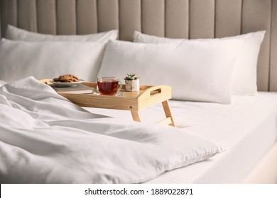 Wooden tray with breakfast and book near soft blanket on bed