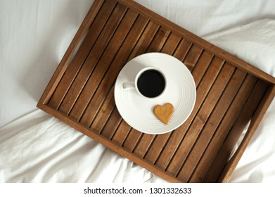 Wooden tray with breakfast on white bed