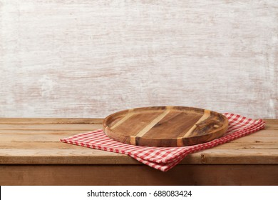 Wooden tray with checked tablecloth on table over rustic background