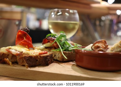 wooden tray of cheese tapas with white wine