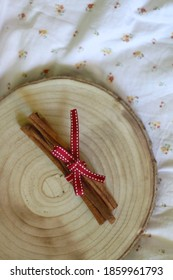 Wooden tray with cinnamon sticks and red ribbon. Top view.
