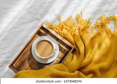 Wooden tray with coffee and warm plaid on white bedding . Breakfast in bed. Hygge concept.