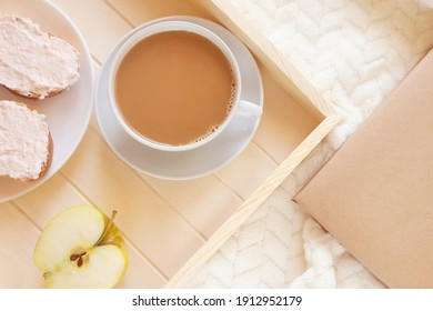 Wooden tray with a cup of coffee and an apple on a light blanket. There is a book nearby. View from above. The concept of a morning, weekend, relaxing home.