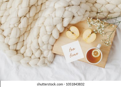 Wooden tray with cup of tea, apple, gypsophila flowers, white merino wool plaid or blanket of thick yarn, card with text TEA TIME on white bedding. Breakfast in bed. Top view.
