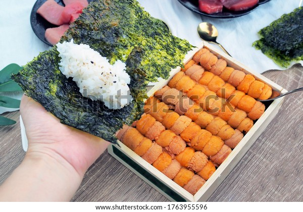 Wooden tray fulled of fresh uni or sea urchin sashimi, Japanese traditional food. Selective focus.