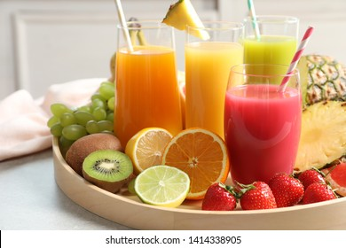 Wooden tray with glasses of different juices and fresh fruits on table