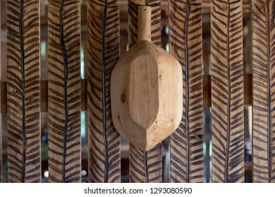 Wooden tray hanging on the wooden wall decorated with stripes engraved in pyrography. Sao Paulo state, Brazil.
