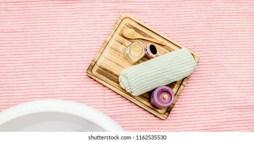 Wooden tray with mustard powder, towel and aroma candle to make foot bath. Against cold illness, congestion, aches and improves blood circulation. Alternative medicine. A lot of copy space.